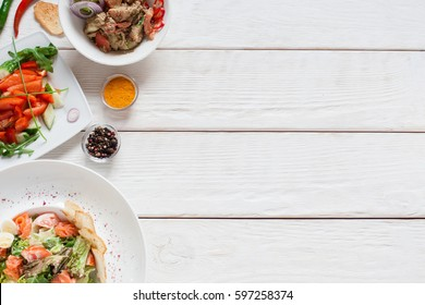 White wooden table with warm salads free space. Top view on kitchen desk with meat side dishes, flat lay. Buffet, banquet, party, menu concept