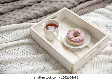 White wooden tray on plaid with pink glazed doughnut and cup of tea in daylight