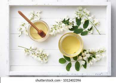 White wooden tray with sweet honey jar and spring acacia blossoms, top view