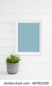 White wooden turquoise background with a plant with a mock up frame for concepts.