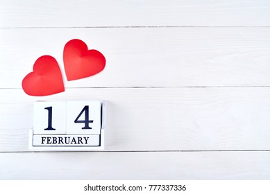 White wooden Valentines Day background with two paper red hearts and wooden block calendar, copy space. Greeting card mockup for Saint Valentines Day. Symbol of love. Love concept, Top view, flat lay