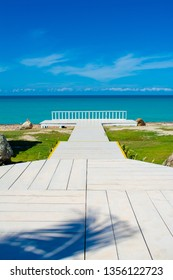 White wooden walkway on a tropical beach, with bright blue sky