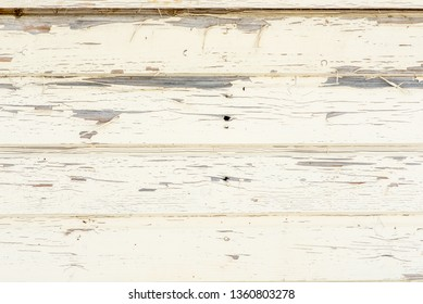 white wooden wall of boards with peeling paint