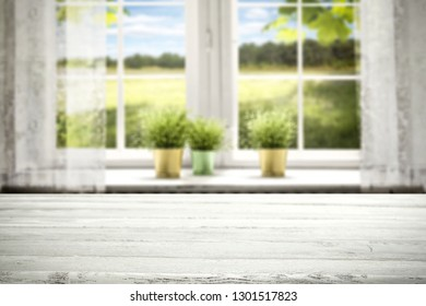 White wooden window background and desk with free space for your decoration. Spring time and green leaves