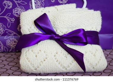 White woolen hand-knit children plaid with hearts bent and tied with a purple bow, close-up