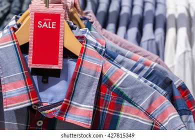 White words FASHION  SALE on a red label, several men's  plaid checkered shirts and   beige wooden hangers, fashion background, close up