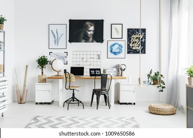 White working area with chairs at desk against the wall with posters in an interior with pouf and plants