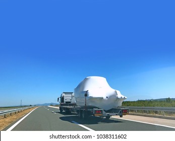 White wrapped boat being transported on trailer