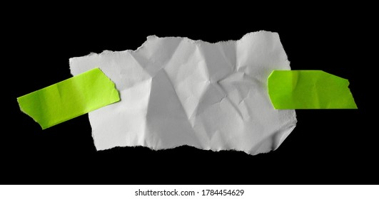 White wrinkly paper scrap with green sticky tape isolated on black background and texture, top view
