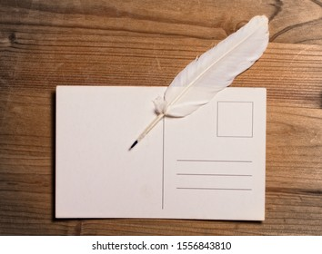 white writing pen lying on top of a clean old post card on a wooden surface