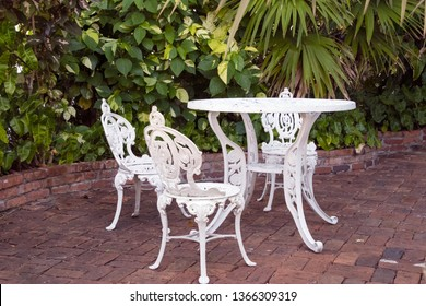 white wrought iron table and chair set on brick patio in tropical garden