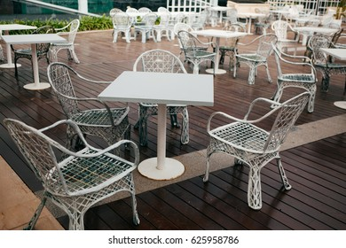 White wrought-iron chairs and tables outside the restaurant
