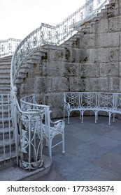 A white, wrought-iron semicircular bench and a fragment of a luxurious openwork staircase leading to the gallery of the Catherine Park. There are no people.