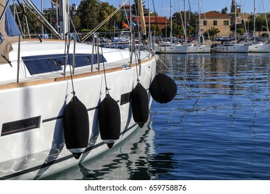 White yacht with fenders in marina