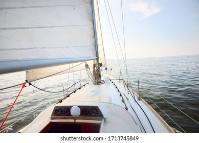 White yacht in an open sea on a clear day. Top down view from the deck to the bow, mast and sails, rigging equipment close-up. Summer Atlantic sailing near Spain and Africa