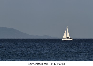 White Yacht. Panorama. Holiday. Journey The Sea. The Ocean. Sailing Boat. Sailboat, White Sail Boat. Blue Sky, Dark blue Sea. An Island on foreground. Navy Blue. Summer Daylight. No Clouds. Landscape.
