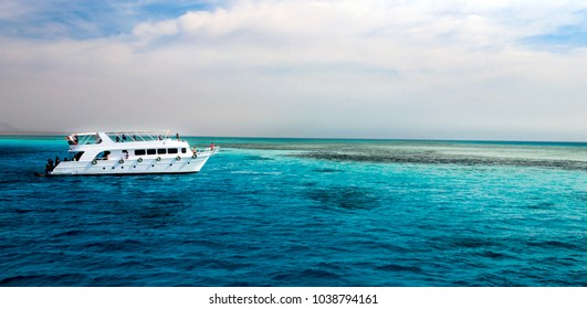 white yacht with passengers sails in the blue azure water of the