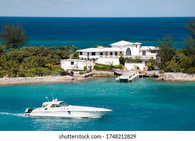 A white yacht passing by the residential house built on a narrow land of Paradise Island between Nassau Harbour and Caribbean Sea (Bahamas).