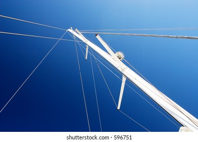 White Yacht sail and radio mast with rolled sails