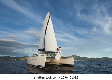 white yacht with sail set goes along the island on a hot day. blue sea, blue sky. on board a young couple in love. the bride and groom. wedding boat trip
