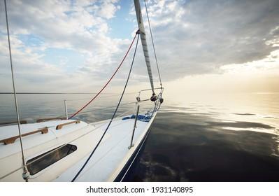 White yacht sailing in the Baltic at sunset. View from the deck to the bow. Glowing clouds, reflections in a still water, natural mirror, soft golden light. Transportation, cruise, recreation, regatta