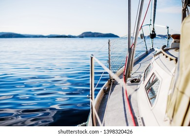 White yacht sailing on a clear sunny day. A view from the deck to the bow, mast and sails. Norway