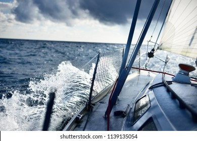 White yacht sailing in an open sea. View from the deck to the bow. Rough weather, storm, dramatic sky, dark clouds, waves, water splashes. Transportation, travel, sport, recreation, leisure activity