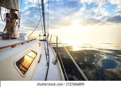 White yacht sailing in a still water at sunset. A view from the deck to the bow, mast and sails. Stunning cloudscape. Natural mirror. Sport and recreation theme. Baltic sea, Latvia