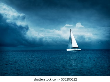 White Yacht Sailing in Stormy Sea. Dark Thundery Night Background. Dramatic Storm Cloudscape. Danger in Sea Concept. Cold Toned Photo with Copy Space.