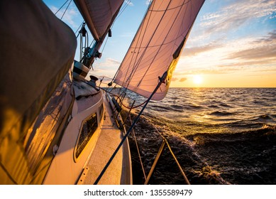 White yacht sailing at sunset. A view from the deck to the bow and sails. Waves and clouds. Baltic sea