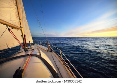 White yacht sailing at sunset. A view from the deck to the bow and sails. Waves and colorful clouds. Baltic sea