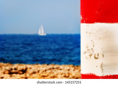 a white yacht seen in the background and out of focus with a bright red and white pillar in the foreground.