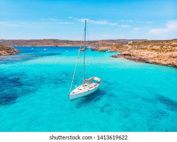 White yacht stands in azure transparent water sea, beach Blue Lagoon Comino Malta. Aerial view.