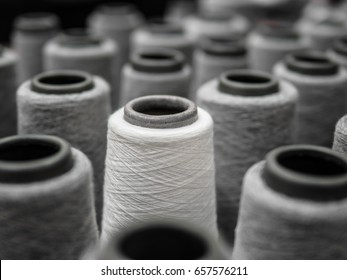 white yarn spools (bobbins) stand out from the crowd of many black yarn spools, Business, leader concept, different concepts, Textile industry concept.
