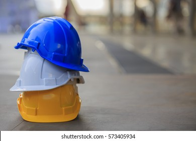 white, yellow and blue hard safety helmet hat for safety project of workman as engineer or worker, on concrete floor