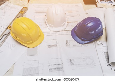 white, yellow and blue hard safety helmet hat for safety project of workman as engineer or worker on desk Side view,Construction plans with on blueprints,Architectural and engineering housing concept.