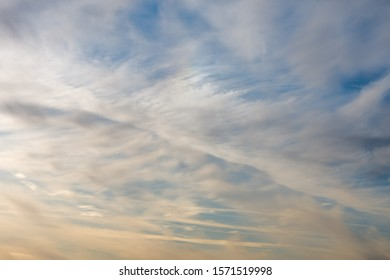 White and yellow clouds float across the sky, feather clouds, the sun is nearing sunset.