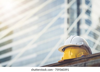 white, yellow hard safety helmet hat for safety project of workman as engineer or worker, on concrete floor on city.