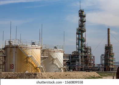 White and yellow oil tanks and distillation column on bright sun at a blue sky on oil refinery plant in a desert.