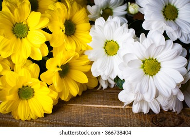 White and yellow oxeye daisy flowers bouquet on wooden background.