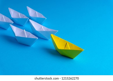 White and yellow paper boat or ship in one direction on blue background. Business for innovative solution concept with selective focus