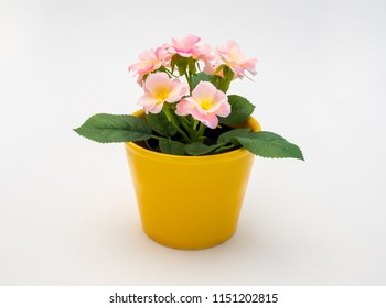 White - yellow - pink plastic decorative flower in a yellow plastic pot is on a white background