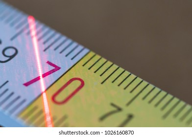 White yellow ruler , red laser beam on it, close up shot on carpentry workshop.