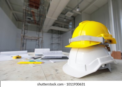 White and yellow safety helmet in construction site, scaffold in background