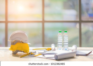 White and yellow safety helmet in construction site with two bottle of drinking water, light from big window in background