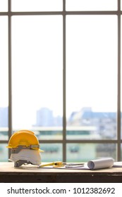White and yellow safety helmet in construction site, light from big window in background