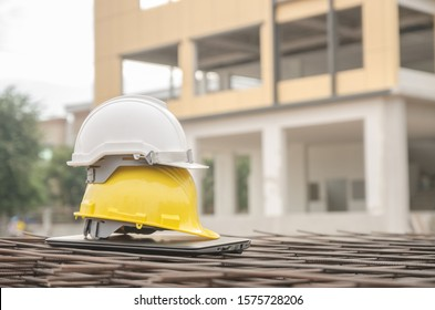 white and yellow safety helmet at construction site with building background