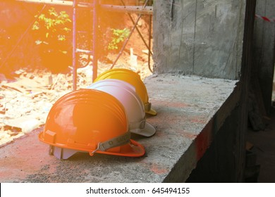 white, yellow safety helmet hat for safety project of workman as engineer or worker, on concrete floor with building on site background.