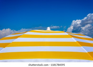 White and yellow sun umbrella on blue sky. Summer holiday