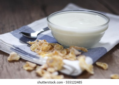 white yogurt in small glass bowl with crispy cereal on cotton cloth place on old wood background.